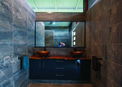 Bathroom Design with marbled tiles, wide wall-mounted mirror and a sink with drawers and cabinets