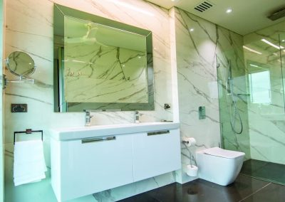 Marble wall Bathroom design with wall-mounted sink and mirror