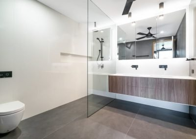 Bathroom With Toilet, Overhead Shower and A Sink divided by glass