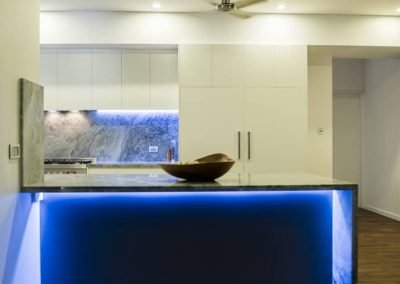 Kitchen with white drawers and cabinets and a built in marble benchtop with blue led lights underneath it