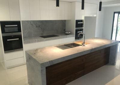 Built in marble benchtop kitchen with wall mounted oven and microwave