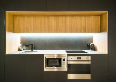Modern Kitchen with wooden overhead cabinets and wall mounted oven